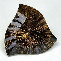 "Smoky Quartz, 49,78 ct, This stone has a true ""smoky"" color, reminiscent of top Swiss Smoky Quartz specimens. It's a rather large gem considering that it weighs nearly 50 carats and the fact that it is virtually eye clean makes it that much more impressive. To top it all off, the stone has a dazzling ""Concave Spinning Trillion"" cut which is unlike any cut I have ever seen."