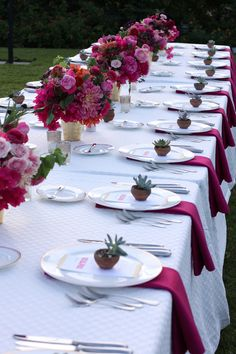 Love the simple treatment of uniform centerpieces down the long dinner table. Pink Flowers and Terrarium Place Settings