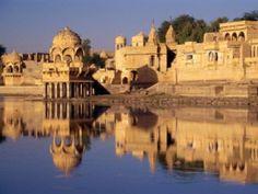 """JAISALMER - A grande atração desta cidade é Jaisalmer Fort, por causa de que Jaisalmer também é chamado como a cidade dourada de Rajasthan. A coisa surpreendente sobre as paredes de arenito são, eles são de cor amarelada que se parece com a cor """"leão"""" na parte da tarde e se transforma em bela cor dourada mágica à noite. Este lugar está situado no coração do deserto de Thar. É um dos lugares magníficos para explorar em Rajasthan onde oferecem arquitetura requintada e rico património…"""