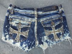 Hand upcycled jeans shorts by 16-year old designer, Sophia Scanlan  Back pocket cross studs with bleach.