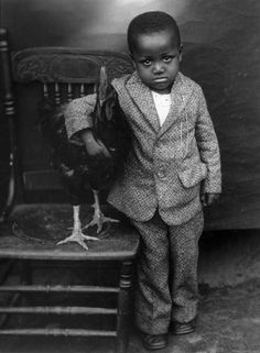 A young boy looks plaintively toward the camera, dressed in undoubtedly his finest wool suit, his prized rooster gently clutched under his arm. c. 1920s-1930s    Columbia, SC    Photograph: Richard Samuel Roberts