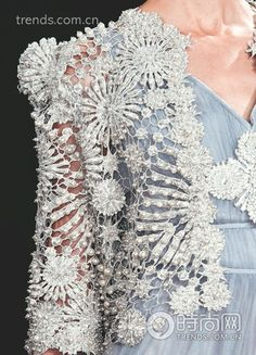 Detail of an Oscar Carvallo (Spring 2013) jacket. Cutwork and bead embellishment really highlight the scrolling floral pattern. Click on the photo to see what the full jacket looks like.  See more of Carvallo's designs at http://www.oscarcarvallo.com/