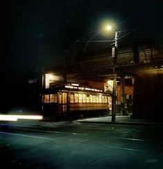 """April 1943. """"Baltimore, Maryland. Trolley leaving the terminal at night.""""(Colorized)"""