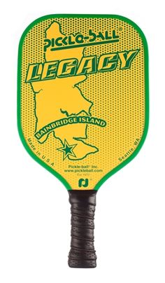 The Legacy Paddle features an image of Bainbridge Island, the birthplace of pickleball. Yellow background with contrasting logo in green, red, blue or black.
