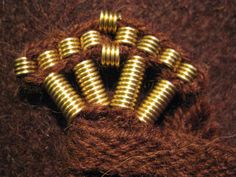 Detail of a finnish iron age mantle for a man: bronze spiral decorations on corners and tablet woven band on edge. Tablet woven by Mervi Pasanen