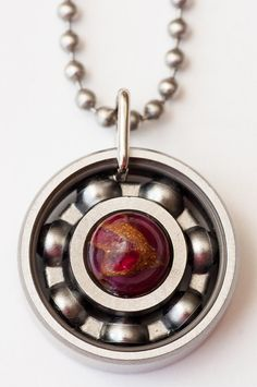 BUY ANY PENDANT, GET ONE 25% OFF with the coupon code: BUYONEGETONE25  This pendant is handcrafted from a skate bearing and Ruby and Pyrite fused with Quartz. (each gemstone bead is different and may not match the photo exactly)  The necklace is a 2.4mm stainless steel ball chain available in 18 or 24 lengths. Pendant jump rings are also stainless steel.  *Like the bearings in your skate wheels, chrome can potentially rust when exposed to moisture, so be careful and dont get your jewelry…