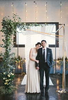 Brides.com: . A modern asymmetrical backdrop with crawling greenery and ribbon streamers, designed by Mimosa Floral.