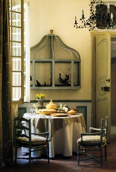 Dining room with a bird cage on the wall.