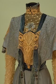 Side Detail TRAINED WOOL AFTERNOON DRESS, EARLY 1900's. Pale blue 1-piece, the high neck lappet bodice with fringe and soutache having dotted net insert and sleeve beneath a shaped wool cape, cream lace insertion and embroidery, back hook & eye closures, skirt has deep swag applique with soutache.