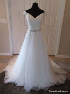 Description Elegant off the shoulder tulle wedding dress with asymmetrical pleating on the bodice accented with a jeweled embellished belt at…
