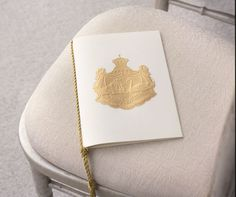 This tasseled program, complete with a personalized gold coat of arms, suggests a regal affair fit for a king and queen.