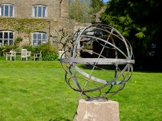 A verdigris armillary with Tropic and Polar rings on a natural boulder