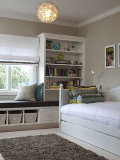Beautiful girl's bedroom with built-ins, floral pendant and bed pillows in Schumacher's Zenyatta Mondatta (peacock).