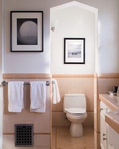 Traditional Bathroom - Artwork hangs in a peach tiled bathroom