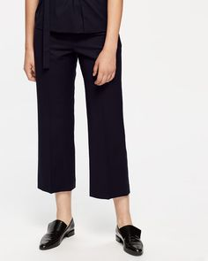 Beautifully simple in design, these flannel trousers are made from wool with a slight stretch for ease of movement. Cut for a relaxed fit with a modern cropped leg, features are minimal and include a concealed zip closure, back welt pockets with a single button and press crease detailing for a formal finish. Pair with matching suit jacket and finish with pointed shoes or leather trainers for contemporary styling.