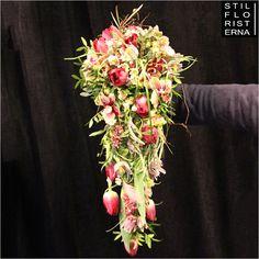 Droppformad brudbukett i hållare, med bland annat tulpaner.
