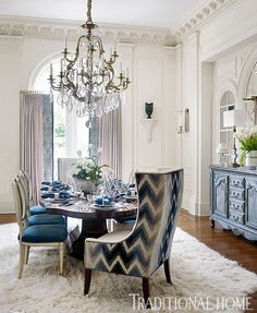 An antique bronze chandelier dazzles above the transitional table, appointed with twin host chairs. - Photo: Emily Jenkins Followill / Design: Randy Korando & Dan Belman