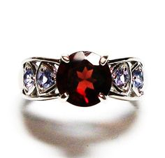 ~~~~~Spice of Life    ~~~~~Gemstone : Mozambique Garnet  ~~~~~Gemstone Shape & Weight : 1.54 ct. 8 mm round ( 4 prong)  ~~~~~Accent Stones : 0.44