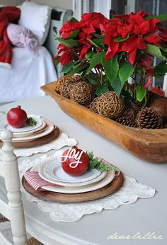 Pretty Christmas tabletop - Poinsettas and pine cones in a dough bowl for the centerpiece, white table and chairs, white scallop edge placemats wiht wood chargers, whte plates, red and white stripe napkins, toped by red ornament and greenery
