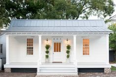How to turn a boring ranch style house into an adorable cottage: add raised (if possible) patio, tin roof, pillars, shutters - Get $25 credit with Airbnb if you sign up with this link http://www.airbnb.com/c/groberts22
