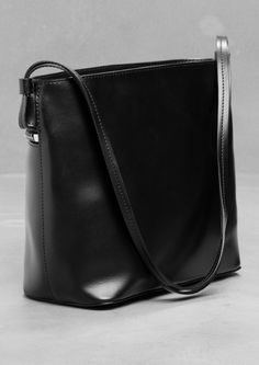 Structured leather shoulder bag | & Other Stories Double leather shoulder strap Zipped outer pocket leads to the main compartment Zipped main compartment Cotton twill lining Zipped pocket, phone pocket, and D-ring for keys Dimensions: 25 x 23 x 11 cm