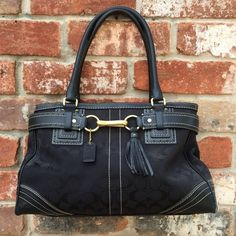 """Great Coach Bag with Tassel Pre-loved authentic Coach bag. Shows signs of wear on the corners and slight wear on the hardware (see fourth picture). Outside of the bag is in otherwise good condition. Inside is in good shape but does show signs of use. Bag measures 14"""" wide, 8"""" tall, and 5"""" deep. Handles have about an 8"""" drop. Great clasp and tassel details on the front of the bag. Coach Bags"""