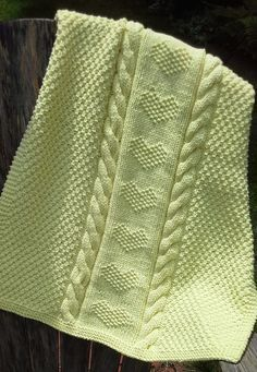 Free Knitting Pattern for Love Is a Blanket - Marji LaFreniere's baby blanket features cables, textured stitches with a column of hearts in the center knit in bulky yarn