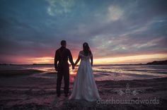 Wedding couple hold hands with beach sunset. Photography by one thousand words wedding photographers