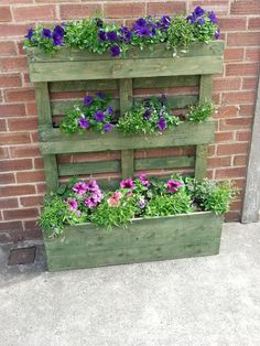 Upright pallet planter stained green Pallet turned on its end with the blocks used as fixing points for slats from another pallet screwed to them to form the planting troughs on the top and