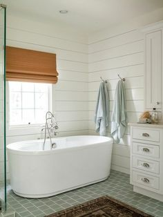 Shiplap walls give this clean bathroom a coastal feel, featuring a white oval freestanding tub, hooks for towels, white cabinets and sea foam floor tile | by Lauren Liess
