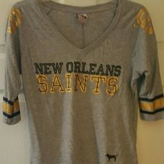 Victoria's Secret Pink NFL Saints tee From Victoria's Secret Pink NFL collection, this top features Saints black and gold colors on the sleeves, shoulder and front. It is in excellent condition. PINK Victoria's Secret Tops Tees - Long Sleeve