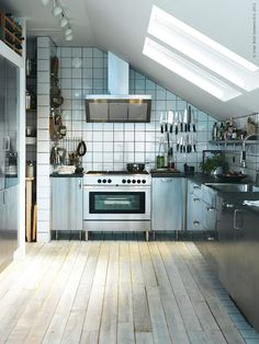 Love everything from the rustic wooden floors, to the stainless steel ikea kitchen and open shelving. Perfect.