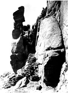 Hopi watching visitors approach the stairway to their mesa-top home at Walpi, Arizona. Photographed by John Hillers in 1873.