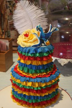 Rio theme cake.  Celebration cake in red, orange, green and blue with Rio at the top. Yellow flower and a feather.