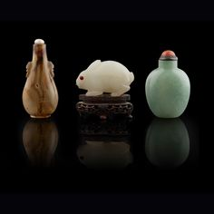 GROUP OF THREE SNUFF BOTTLES QING DYNASTY, 19TH CENTURY the shadow agate bottle of flattened pear shape on a short foot, a pair of mock animal mask and ring handles carved to the shoulder; the white jade bottle carved in the shape of a rabbit; the green jade bottle of flattened ovoid shape (3) largest 7cm high