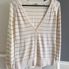 Banana Republic cream and metallic gold cardigan. Banana republic cream and gold metallic cardigan.  V neck button down. Size small. Small blemish on back as noted in photo. Price reflects flaw. Not easily seen with longer hair. Banana Republic Sweaters Cardigans