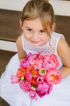 Summer flower girl outfit idea - white dress with polka dot details and bright, pink bouquet {Photo by @pinriverland}
