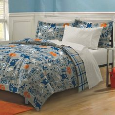 The fun comforter and sham display skateboarders, lightning, triple-X logos, boom boxes and skater slang in blue and white punctuated by skull logos in orange on a grey background. The coordinating sheets feature a geometric pattern in charcoal and white.
