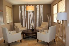 Modern nature inspired living room incorporates four Lazar chairs, brown and beige color scheme with yellow accents and bold birch tree decals on accent wall.
