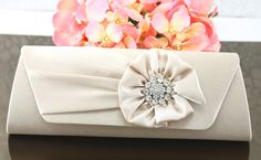 """Wedding Clutch Wedding Purse Bridal Clutch by goddessdesignsgems, $54.00 """"Absolutely beautiful design"""" this gorgeous satin clutch in a shimmering Champagne (light tan) color features a pleated front flap embellished with a sparkling crystal silver brooch nestled inside a gorgeous satin flower rosette for a very rich & elegant look. Magnetic clasp closure under the front flap easily secures items inside."""