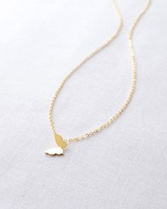 Butterfly Necklace by Olive Yew. Sweet little silver or gold butterfly charm looks beautiful layered with other necklaces or worn alone.