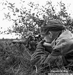 Belgium - Corporal G.E. Mallery covering other members of the Scout Platoon, Queen's Own Cameron Highlanders of Canada, advancing towards Fort de Brasschaet. October 9, 1944. Belgium