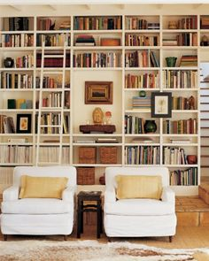 Light library space, with lovely white armchairs and floor to ceiling bookshelves, artfully stocked.  Floor to ceiling bookshelves with ladder.