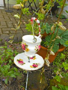 Alice in Wonderland inspired garden art.  Recycled Vintage cup and saucer, silver spoon and old beads.  More in production and available on my website soon.