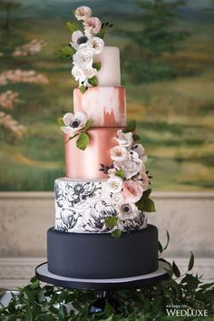 Rose gold wedding cakes are one of my favorites! Black cake tier followed by a painted tier of black and white flowers and tiers of metallic rose gold. Cascading fresh or silk flowers.