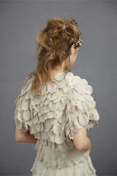 Interesting idea - but bulky.  Something lighter?  Overlapping disks of boiled wool are sprinkled with iridescent seed beads and interspersed with crocheted lace petals. Wool, linen, cotton; silk lining.