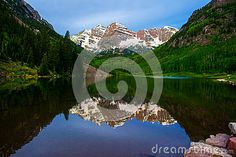 The infamous maroon bells near Aspen , Colorado are one of the most amazing places on earth. the 14,000 foot peaks rise right above a near perfectly still lake if you have the time to wait for it to become still.   Perfect still Crate lake makes a mirror reflection of the maroon bells in june with a little snow on top and spring almost summer like conditions down on the bottom of the valley