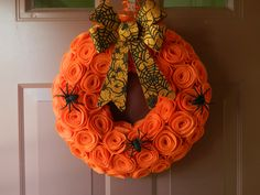 Halloween Wreath - Felt Wreath with Orange Rosettes and a Black and Orange Glitter Bow and Spiders - 14 inch. $ 48.00, via Etsy.