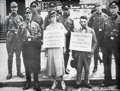 """A Jewish man and a non-Jewish woman pilloried by Nazi officers, presumably for an alleged involvement, Cuxhaven, Germany, July 1933. Her sign reads: """"I am the biggest pig in the town and only get involved with Jews!"""", and his sign reads: """"As a Jewish boy, I only go to bed with German girls"""". The man might be Oskar Dankner, owner of a cinema in Cuxhaven."""