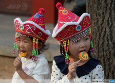 CHINA, BEIJING : Young Chinese tourists eat lollipops during their visit to Tiananmen Square in Beijing on October 3, 2013. Chinese tourists should not pick their noses in public, pee in pools or steal airplane life jackets, China's image-conscious authorities have warned in a handbook in their latest effort to counter unruly behaviour. AFP PHOTO/Mark RALSTON